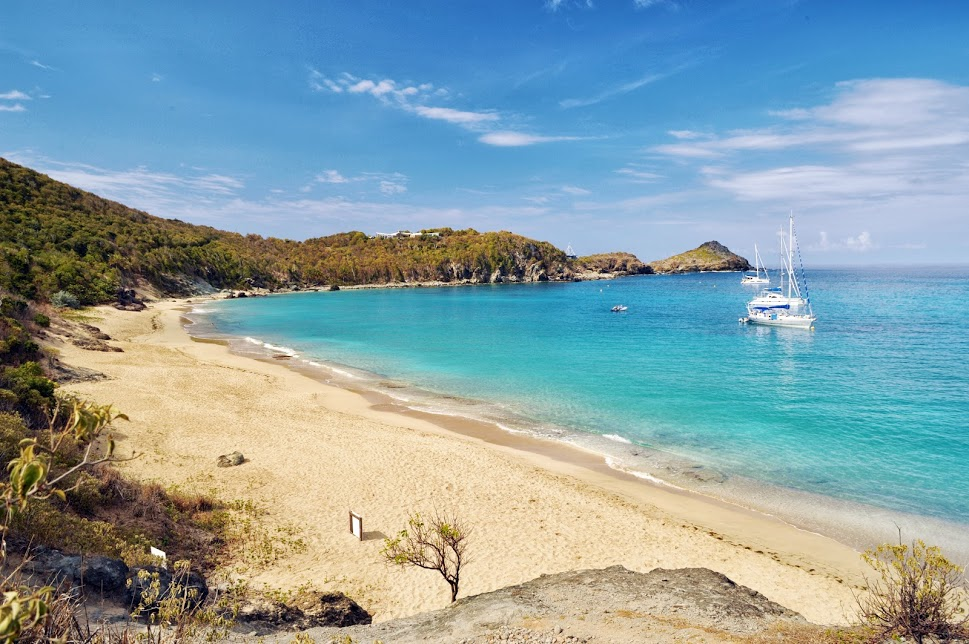 St. Barths Colombier beach with blue water and sail boats anchored.